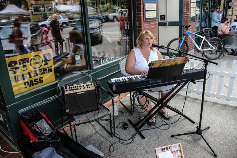 Meg Josalen playing original songs under the awning.