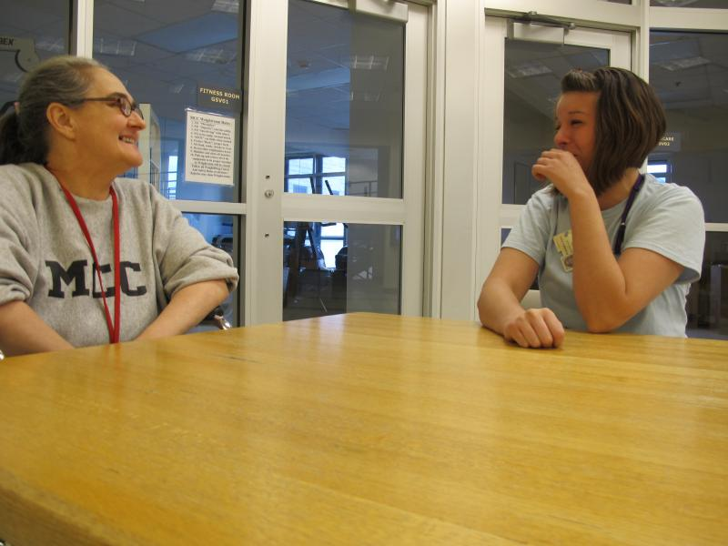 "Jodi Holmes (left) and Kara Bouchard converse at a table in the ""mall"" area at the Maine Correctional Center in Windham."