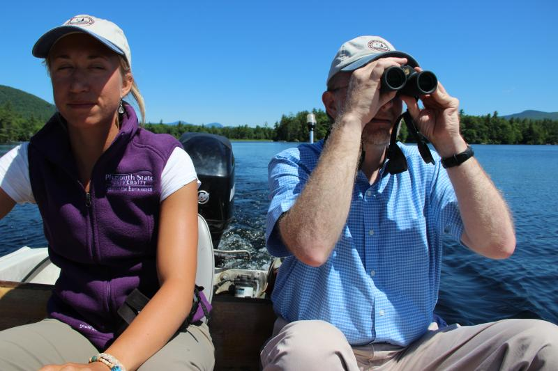 Biologist Melisa Leszik steers the boat while LPC Director Harry Vogel looks for loons.