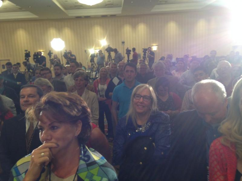 The crowd at Brown HQ watches his victory speech