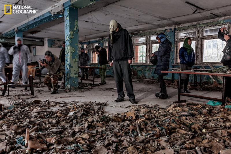 Gas masks, common in Soviet schools, were scattered on the floor, creating a popular sightseeing spot. One tourist brought a mask to put on for photos.