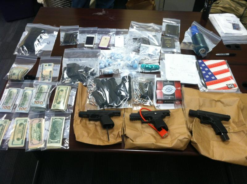 Guns, cash, cell phones and packaging materials seized.