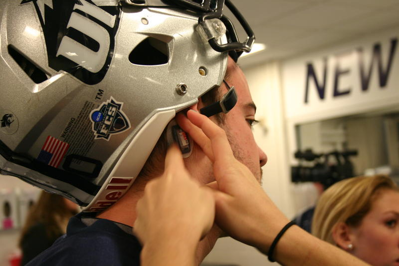A student researcher plants a sensor behind a player's ear.
