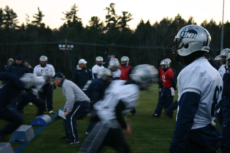 Head Coach Sean McDonnell (L) crouches and in front of his team as they run a drill.