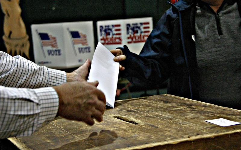 A voter hands in a ballot in Colebrook