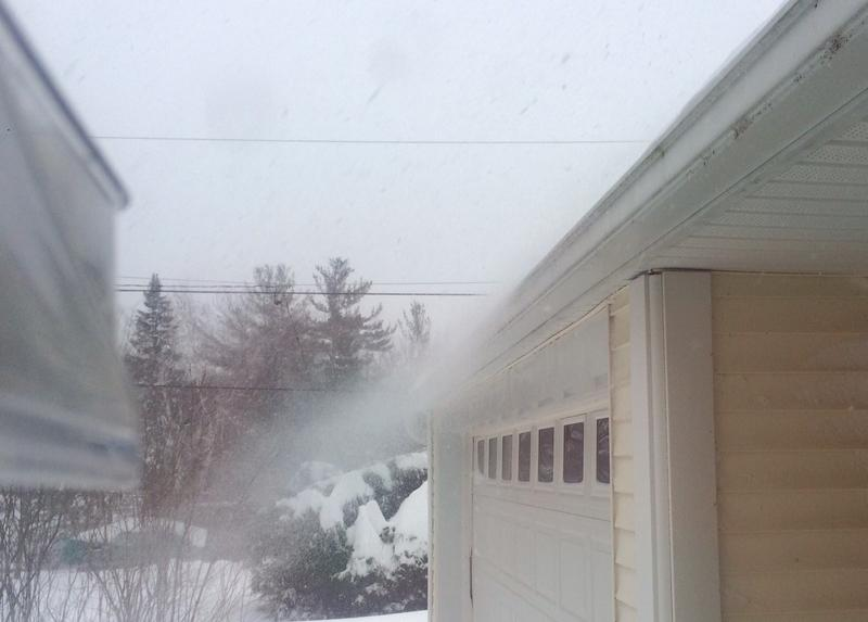 Snow blows off a roof in Hollis