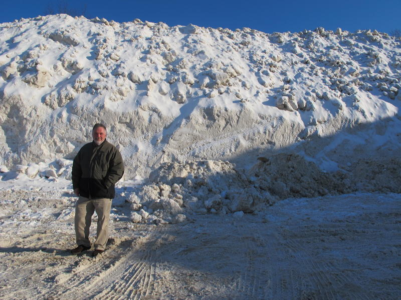 Portsmouth Mayor Bob Lister stands at the foot of a massive snow pile