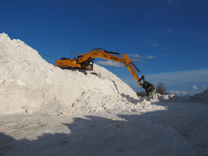 An excavator on the pile scoops up the snow
