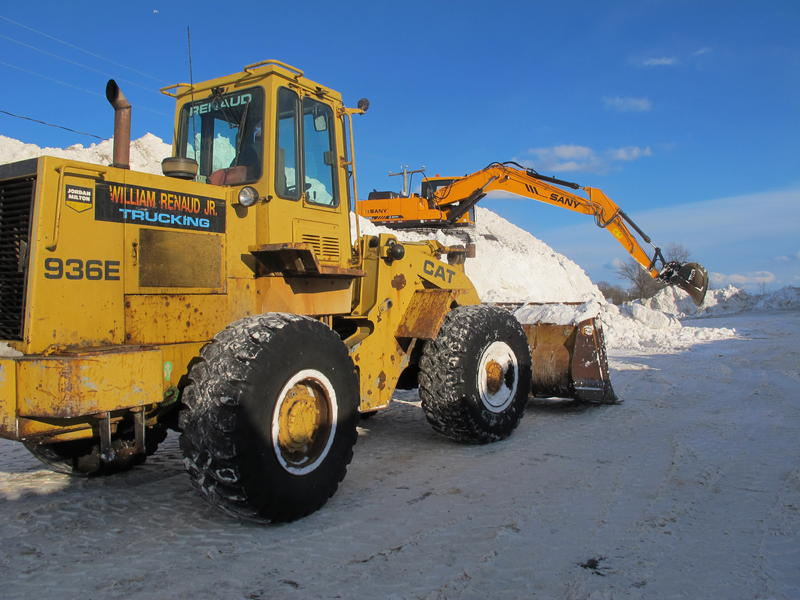 A front loader delivers snow to the foot of a fresh pile