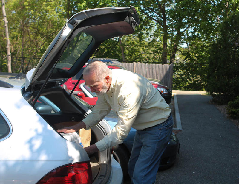 Volunteer David Gilmour packs his car with meals at the Nashua Senior Center