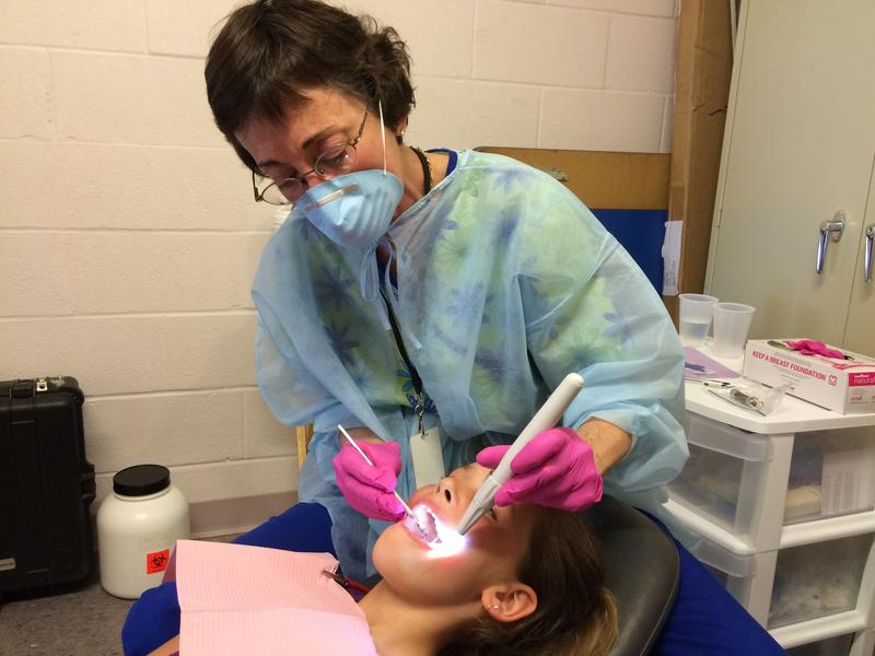 Oral hygienist Kyle Messier cleans a student's teeth in a storage closet in Maple Avenue Elementary in Claremont.