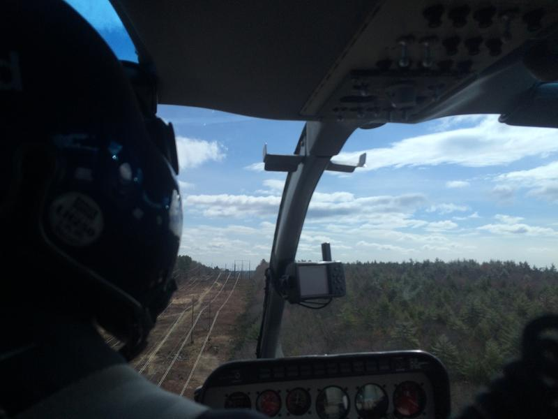 Kurt Nelson, an arborist with Eversource, rides shotgun on a helicopter patrol of transmission lines in Southern New Hampshire.