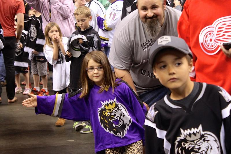 Alexa Lavalle, in purple Monarchs shirt, waits to give players a high-five with her dad, David Lavalle, of Londonderry.