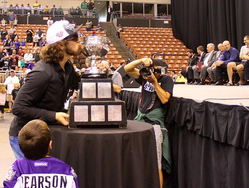 Monarchs goalie Patrik Bartosak kisses the Calder Cup on his way to the stage, as a young fan looks on.