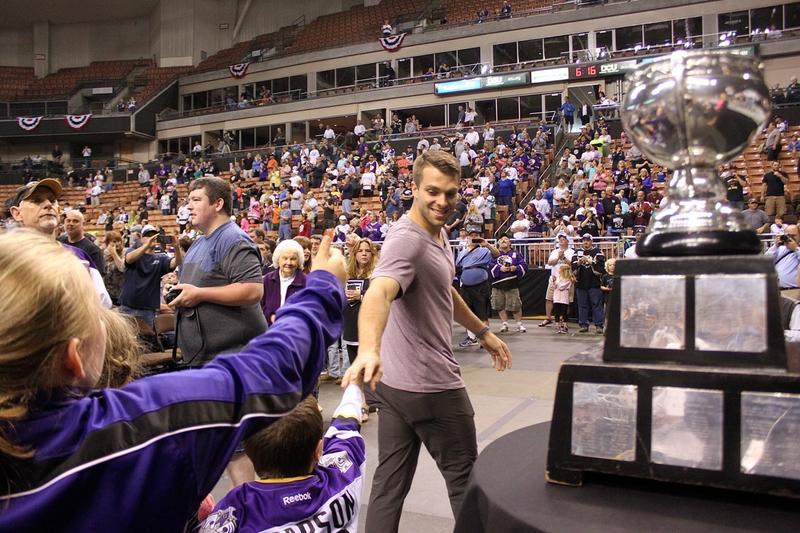 Monarchs goalie Steve Mastalerz walks past the Calder Cup as fans reach out for a handshake.