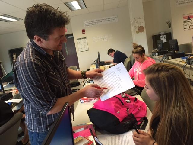 "Nashua High School South English teacher Rob Greene goes over an essay with a student. The district is experimenting with an ""unleveled"" freshmen writing class."