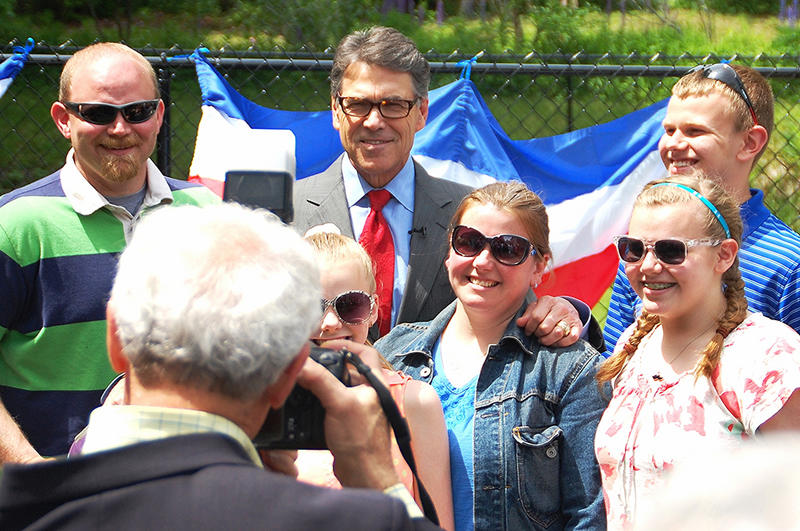 Former Texas Governor Rick Perry poses for photos at a house party in Meredith, June 7, 2015.