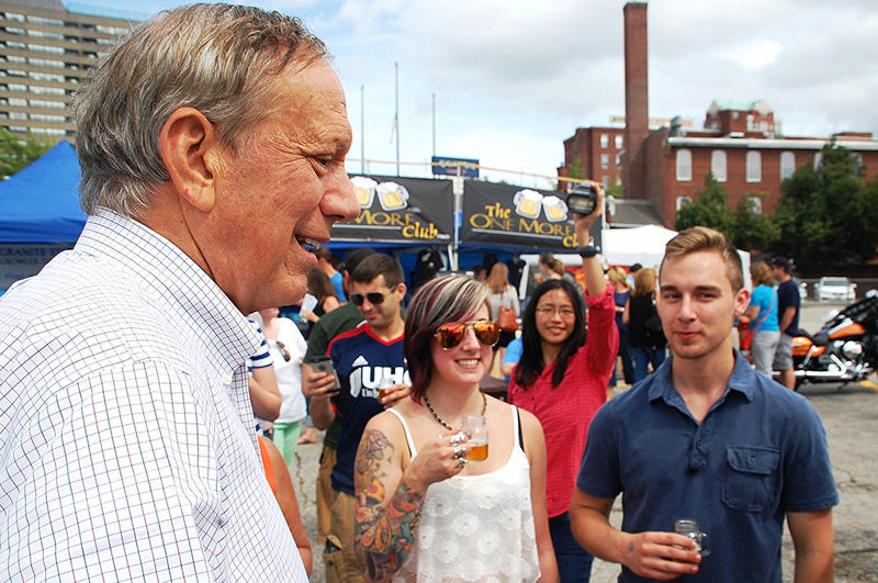 Former New York Governor George Pataki (left) talks with participants in the Granite State Brewers Association Summerfest in Manchester, July 25, 2015.