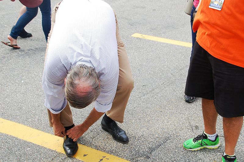 Former New York Governor George Pataki pauses to tie his shoes at the Granite State Brewers Association Summerfest in Manchester, July 25, 2015. Pataki, who had to do this three times at the event, joked he'd be better off taking his shoes off.