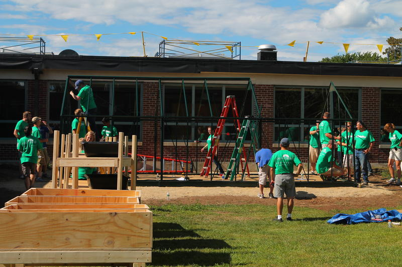 Volunteers help construct the greenhouse at Elm Street School