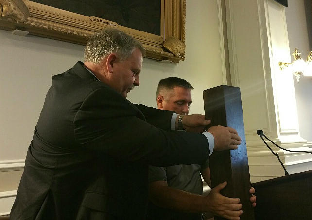 Speaker Shawn Jasper assists Mark Battey with the striking post, made of NH walnut harvested by Joe Butts from the property of Eileen Devine.
