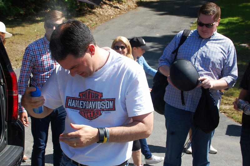 Wisconsin governor Scott Walker sprays on sunscreen ahead of his New Hampshire motorcycle tour, September 6, 2015.