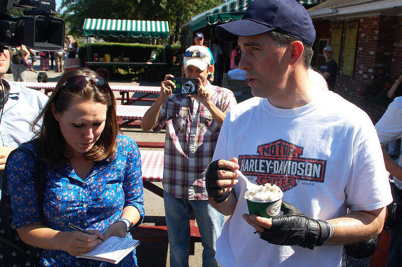 Wisconsin Governor Scott Walker (right) talks with reporters while eating chocolate chip cookie dough ice cream in Jaffrey, New Hampshire, September 6, 2015.
