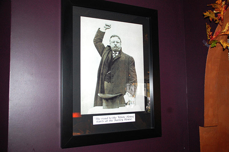 """A picture of former President Theodore Roosevelt greets visitors, with the slogan """"The road to the White House starts at the Barley House."""""""