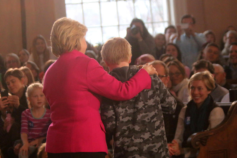 Clinton stands beside one of the four children she called on in Portsmouth at South Church.
