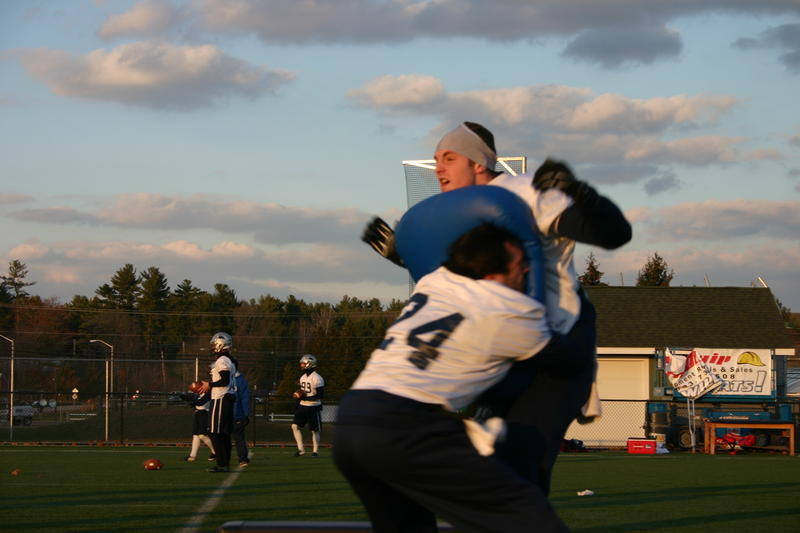 UNH Wildcats practice a tackling drill without helmets under the observation of researchers.