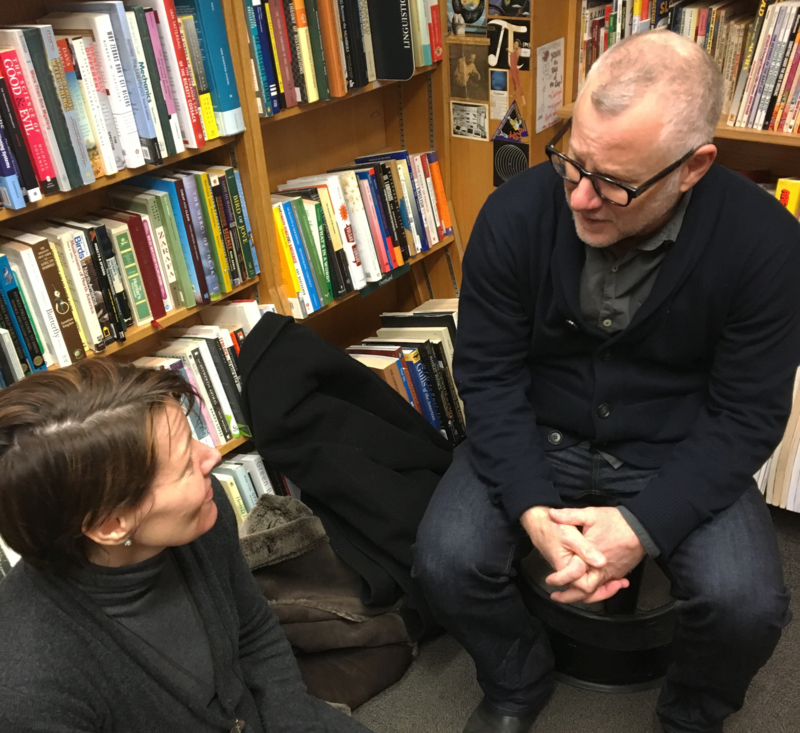 Virginia sits on the floor to interview Tom Perrotta at Harvard Book Store.