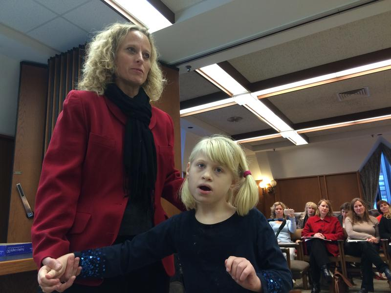 Amy Girouard of Concord testifies to the Governor's Commission on Medicaid Care Management with her daughter, Alison, at her side.