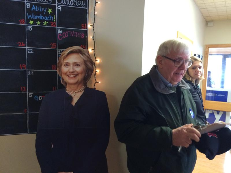 An organizer stands by a cardboard sign of Hillary Clinton at a canvass event in Salem.