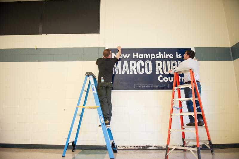 Campaign workers hang a sign for Rubio before a Londonderry event Saturday morning, hours before the candidate stumbled in the final GOP debate before the primary