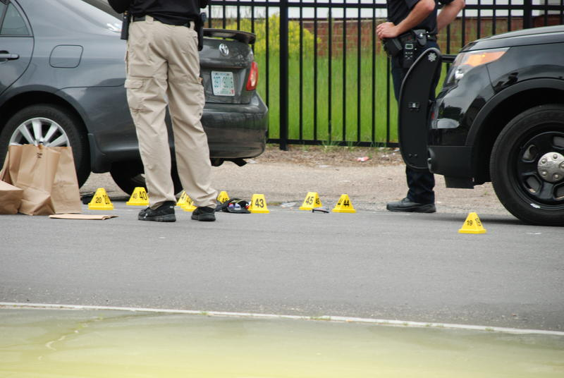 Police investigate the scene of this morning's shooting on Ferry St. in Manchester