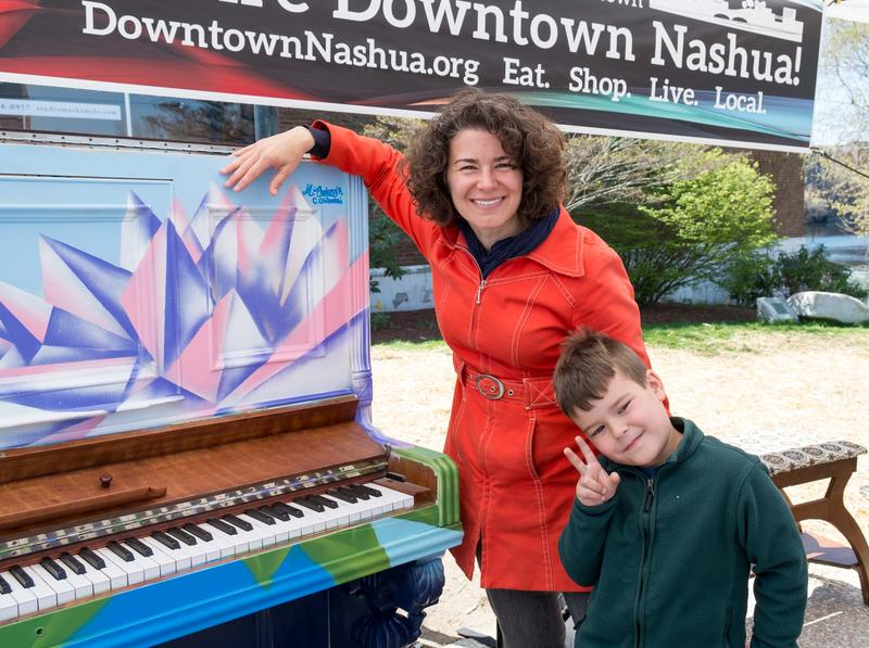 Sarah Roy and her son Ben pose by a piano