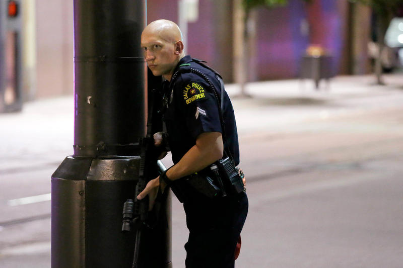 A Dallas policeman keeps watch on a street in downtown Dallas on Thursday.