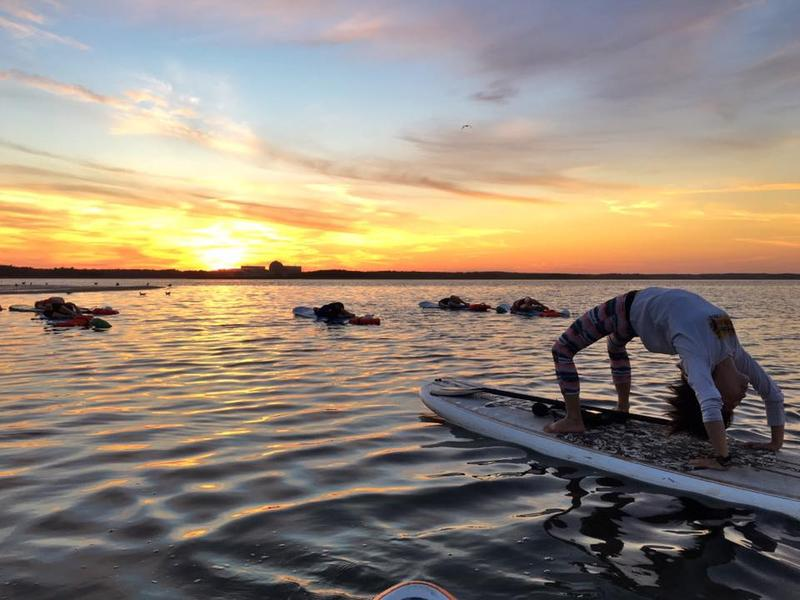 Reporter Pien Huang balances her recording kit with a backbend on a stand-up paddleboard