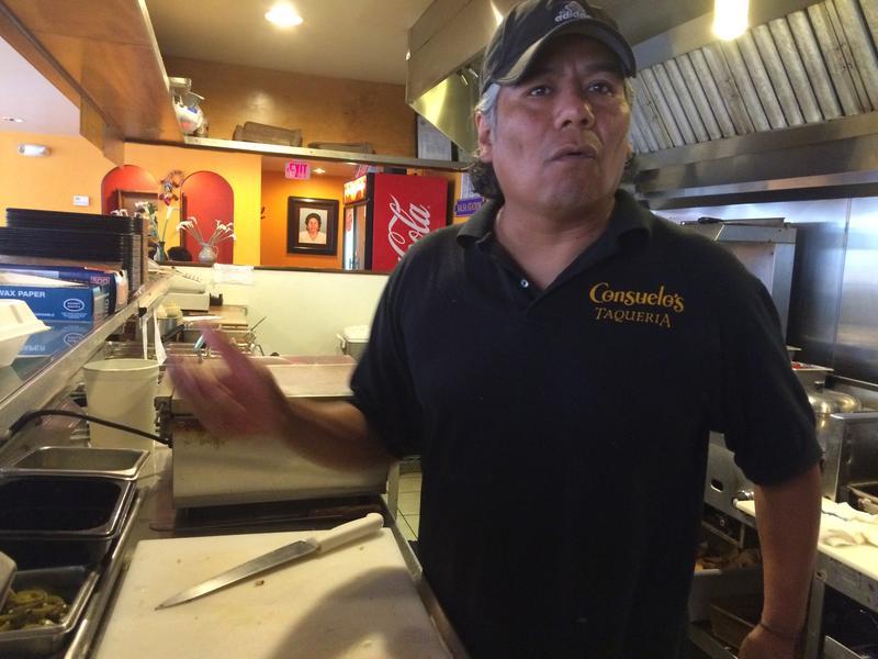 Martin Delgadillo stands behind the counter of his Manchester restaurant, Consuelo's Taqueria.