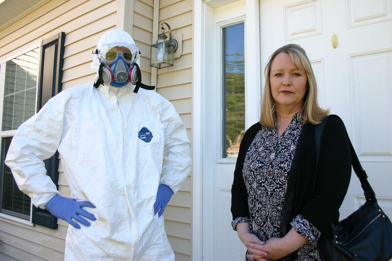 Dan and Dawn Crim stand on the front porch of the Laconia home they fled in 2014. They say shoddy construction and water infiltration led to mold and yeast, which in turn made them and their son sick.