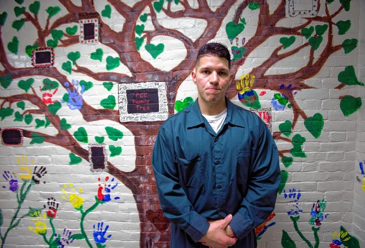 Evanor Pineda, a father of two, stands in front of the Family Connections Center family tree at the state prison in Concord.