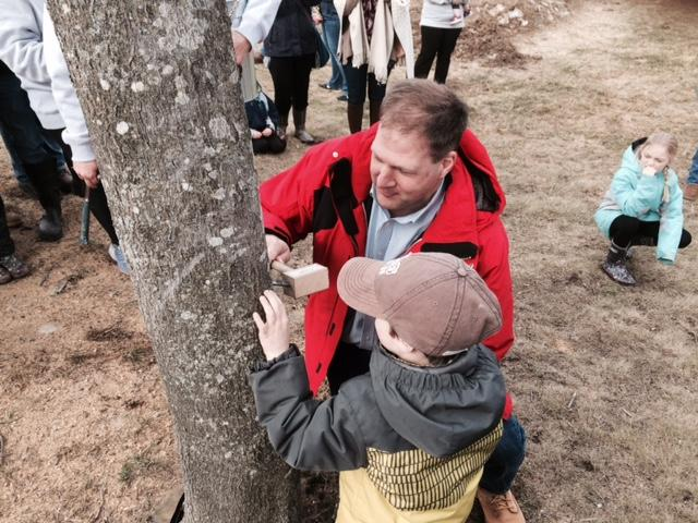 Governor Chris Sununu taps a maple tree with his four year-old son Leo