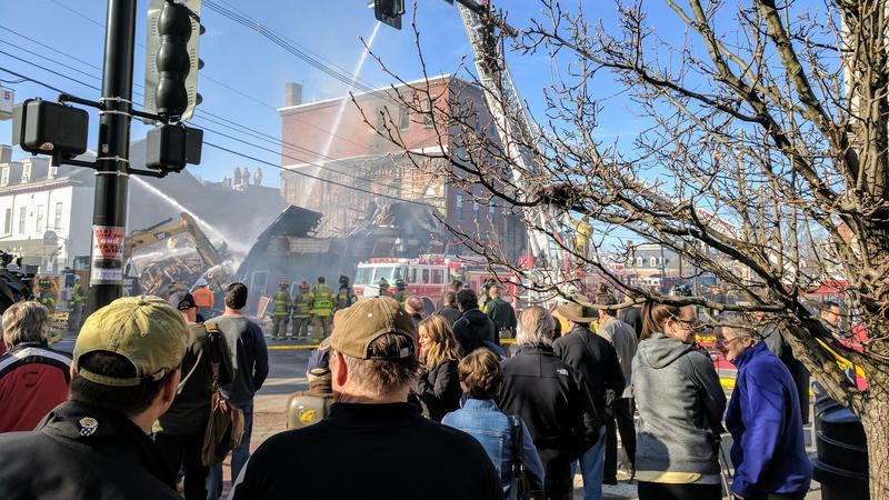 A crowd gathered Monday morning to witness fire crews battle a still-smoldering fire on State Street in Portsmouth.