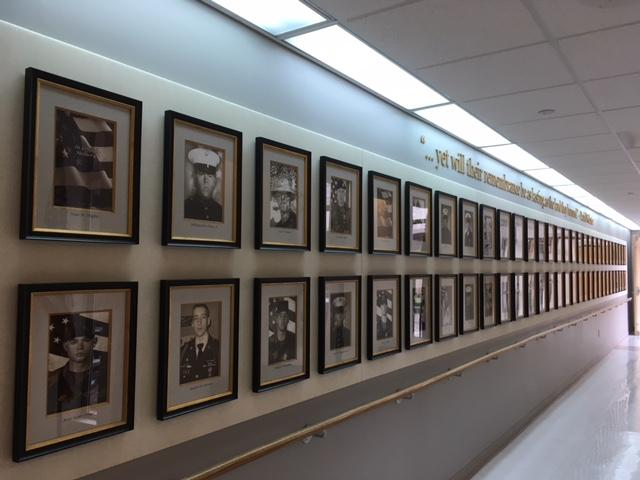 """60 soldiers from New Hampshire died in Combat between 2001-2017. Their images line a """"wall of valor"""" at the Manchester VA."""