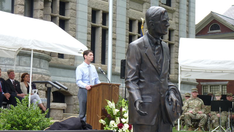 In the foreground, a new statue of John Winant. Speaking at the podium is the artist who made the work, Brett Grill.