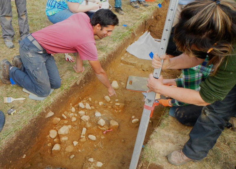 Volunteers unearth a rock cluster at the SCRAP field school in 2015.