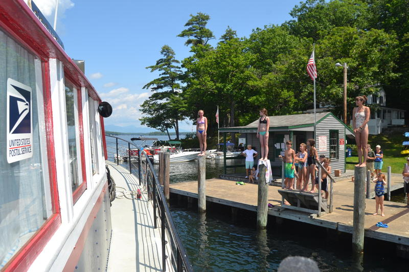 The Sophie C. - Lake Winnipesaukee's famous mail boat - departs Bear Island as kids wait to jump in her wake.
