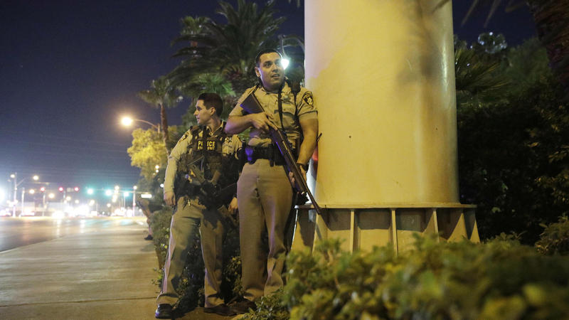 Police officers take cover near the scene of a shooting near the Mandalay Bay Resort and Casino on the Las Vegas Strip on Sunday.