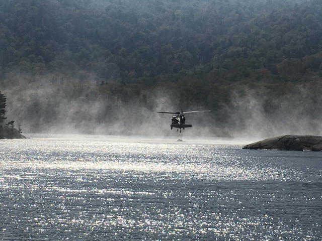 A helicopter resupplies with water to attack forest fire.