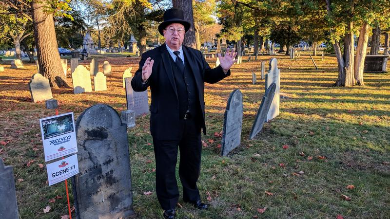 Local attorney Mark Moeller portrays Nathaniel Ela, a 19th century tavern owner, while standing next to his grave.